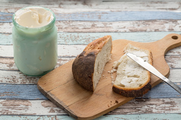 Clotted cream (slivki) on slice of loaf bread on cutting board on vintage table