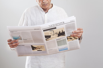 Portrait elderly man reading newspaper