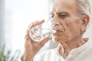 Portrait elderly man drinking water