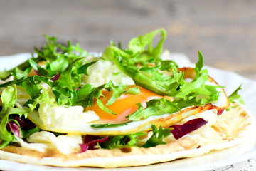Fried egg crispy tortilla with salad mix and hummus on a plate. Healthy vegetarian tortilla with filling. Closeup