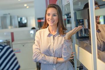 Saleswoman presenting coffee machine