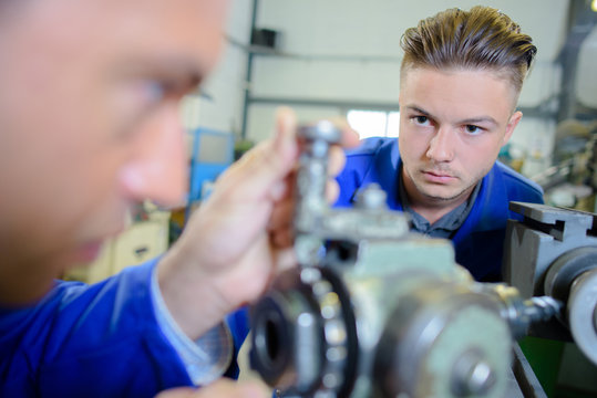 engine assemblers working on a machine
