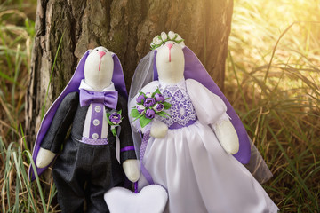 Easter rabbits, bunny toys in shape wedding couple in forest. Textile bride and groom