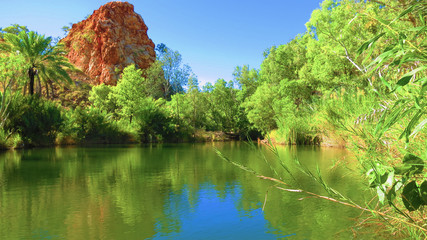 River with rock formation in background and plantations near Palm Springs campsite in halls creek, Western Australia