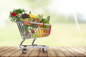 Einkaufswagen gefüllt mit frischem Obst und gemüse.