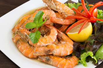 Shrimp boiled with honey and salt  in white dish on dark table