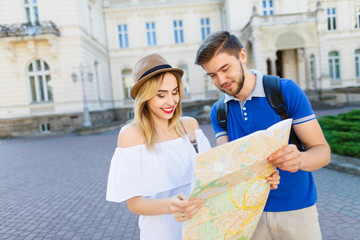 Attractive couple standing with map