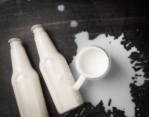 Milk bottle and Milk spilled on dark wood,top view
