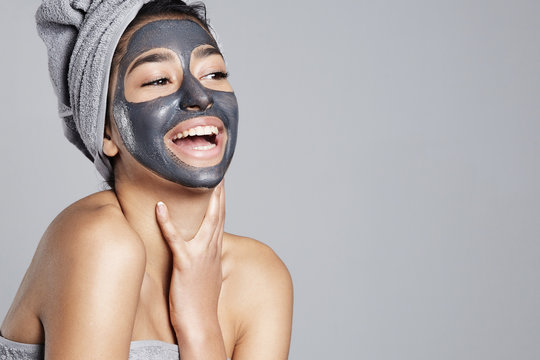 laughing woman having fun with facial mask on