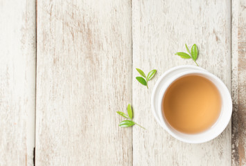 Cup of tea and tea leaves on wooden,top view