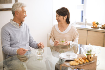 Senior couple drinking tea at dining table, smiling