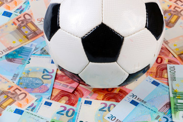 Playing field of paper euro notes and leather soccer ball