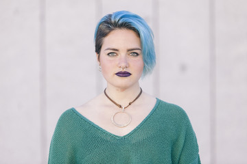 Teen androgynous woman with sad expression and blue dyed hair isolated on the street