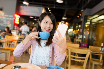 Woman taking selfie by mobile phone in cafe