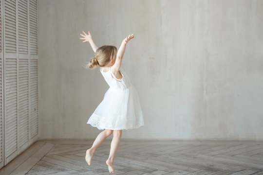 A little girl dancing in a room in a beautiful dress