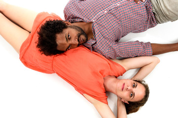 Interracial couple is lying on the floor embracing their love.