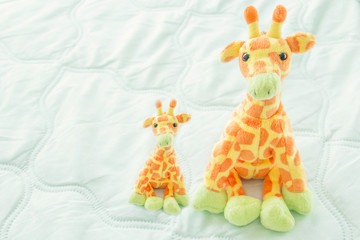 Two giraffes cute are seating on green fabric,Mom and baby giraffes