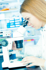 woman with microscope in microelectronics laboratory