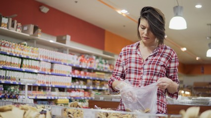 Young woman choosing biscuits and shortcakes at the supermarket. 4k