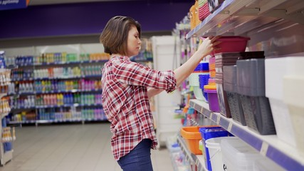 A young woman in check shirt is choosing plastic box in the shopping center. 4k