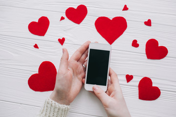 valentines day.female holding smart phone on white wooden background with red hearts