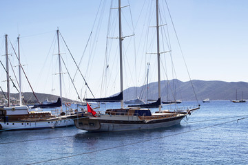 Luxury yachts (sailing boats) parked on turquoise water in front of Bodrum castle. The image shows Aegean and Mediterranean culture of coastel lifestyle.