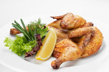 Chicken grilled and served with green salad on a white background