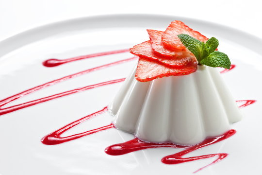 Panna cotta dessert with strawberries on a white plate . Close up