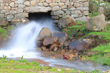 Water stream coming out of a traditional old water mill in full activity