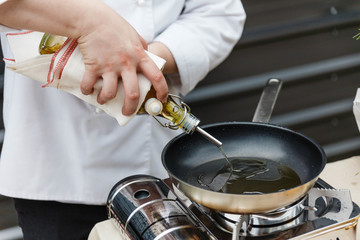 Chef Pouring Rosemary Oil in Pan, Ready to Cook.