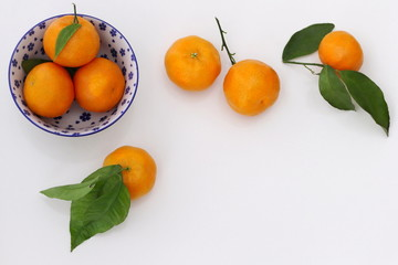 Top view of a fresh mandarin orange fruits with leaves on a white background. Ripe orange tangerine citruses frame. Photo from above.