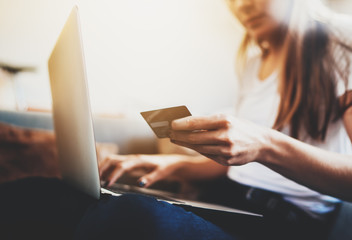 Closeup of female hands holding credit card to pay online via modern laptop, hipster girl with long hair using debit card paying for shopping online in internet, flare light