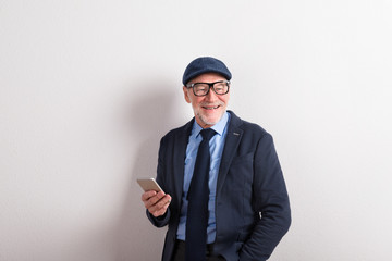 Senior man in blue shirt, jacket, eyeglasses and cap, holding sm