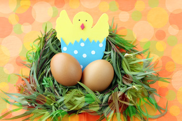 easter decoration: yellow eggs and hand made hatched chicken in eggshell in green grass twigs nest on bright colorful  background with copy space