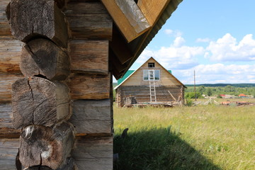 Wall Mural - Log building baths against a wooden house and blue sky  in the remote Russian village in the summer