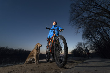 Bicyclist with a dog on the river