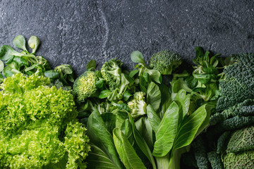 Variety of raw green vegetables salads, lettuce, bok choy, corn, broccoli, savoy cabbage as frame...
