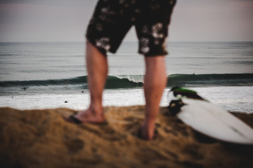 View of a wave breaking through a surfer's legs