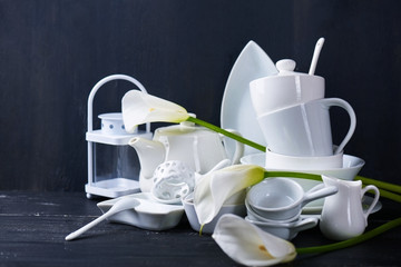 Set of new white dishes with teapot, tea cups, and plates on a black wooden table with fresh callas
