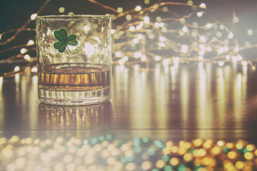 Irish Whiskey St Patricks Clover Golden Glow. Irish whiskey in a glass with a clover symbol, on a pub table with gold beads and bar lights.