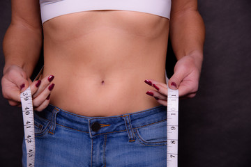 A Woman Measuring Her Waist Close Up