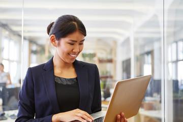 Asiatische Frau schaut auf Tablet Computer