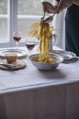 Woman serving tagliatelle pasta with black truffle from the vintage bowl