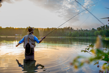 Young man flyfishing at sunrise Wall mural