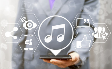 Music live streaming social media network business online web concept. Man offer smartphone with melody icon on virtual screen. Sound track broadcast and download, internet website stream technology