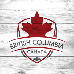 A Canadian province crest on a background of distressed barnboard. The shield features a maple leaf and the main text says British Columbia, Canada.