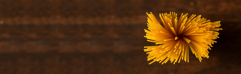 Gluten free pasta on dark background. Top view of raw spaghetti.