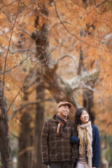 Couple Walking In the Woods In Autumn