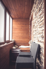 Cabin lodge interior in vintage nautical style decorated with wood planks and stone with big windows wooden barrel and bar chairs in rustic style