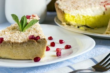Homemade coconut cream pie and pomegranate seeds in white plate